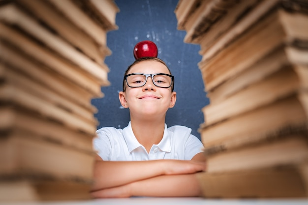 Happy smart boy in glasses sitting between two piles of books with red apple on head and look at camera smiling.