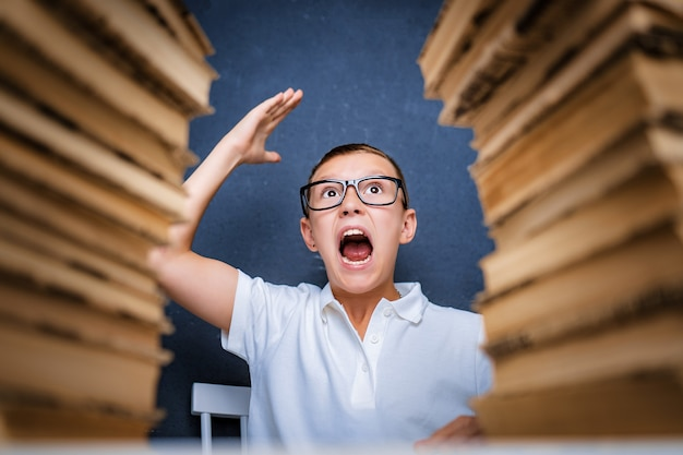 Счастливый умный мальчик в очках сидит между двумя стопками книг и улыбается.