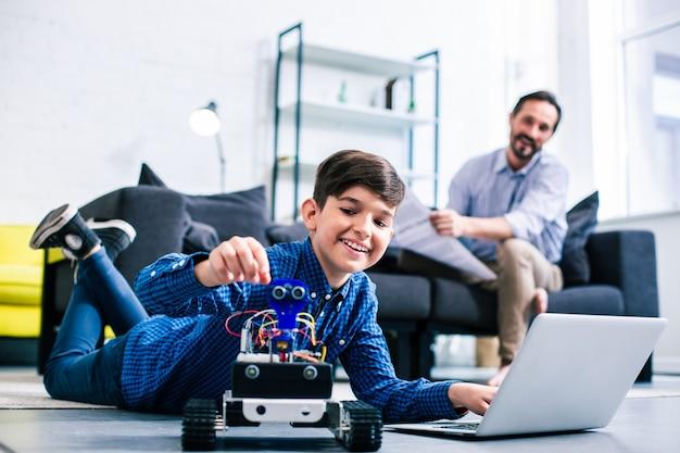 使用中のロボットをテストしながら床で休んでいる幸せな賢い少年