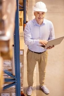 彼の従業員の仕事を制御しながら彼のラップトップのボタンを押すと幸せなスマートビジネスマン
