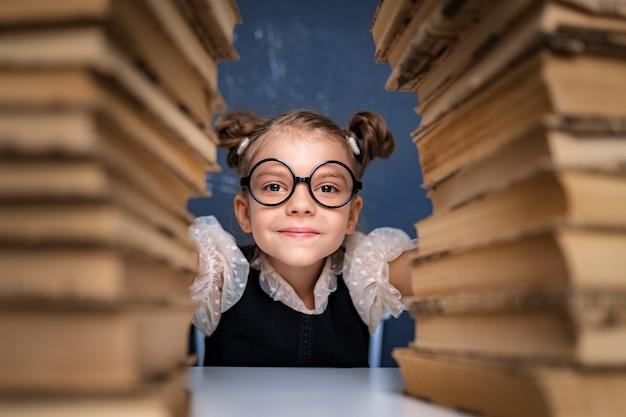 Счастливая умная девушка в округленных очках сидит между двумя стопками книг и смотрит на камеру, улыбаясь.