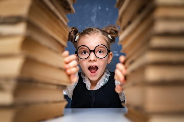 本の2つの山の間に座って丸みを帯びたメガネで幸せなスマートな女の子