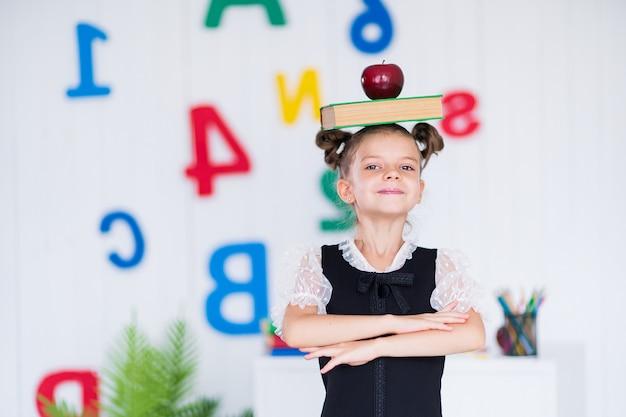 Счастливая умная девушка в школьной униформе держит книгу и красное яблоко на голове, смотрит в камеру.