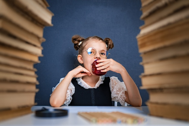 Happy smart girl in rounded glasses, eating a red apple while sitting between two piles of books and look at camera smiling.