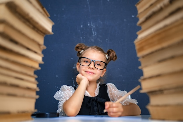 Happy smart girl in rounded glasses, holding a pencil in hand ready to write sitting between two piles of books and look at camera smiling.
