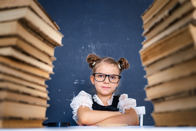 Happy smart girl in rounded glasses sitting between two piles of books and look at camera smiling.