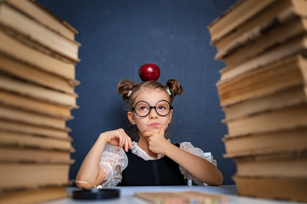 Happy smart girl in rounded glasses thoughtfully sitting between two piles of books with red apple on head, pointing finger and look at camera smiling.
