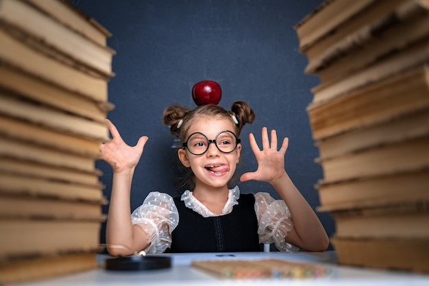Happy smart girl in rounded glasses with red apple on her head sitting between two piles of books, have fun and look at camera smiling.
