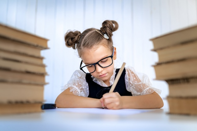 Happy smart girl in rounded glasses, writing, drawing while sitting between two piles of books.