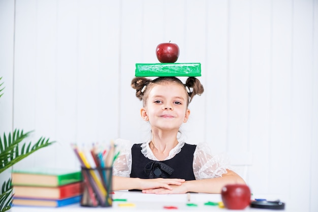 Happy smart girl in school unifrom hold book and red apple on head, look at camera.
