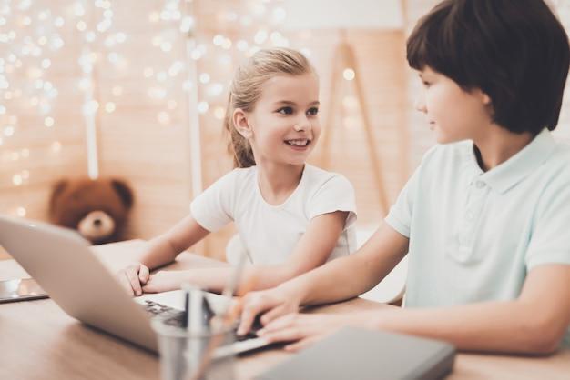 幸せなスマートな子供たちはラップトップで宿題をします。