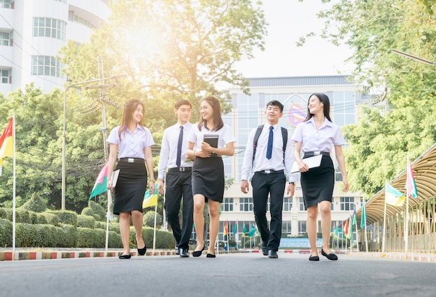 Happy and smart student walking on road