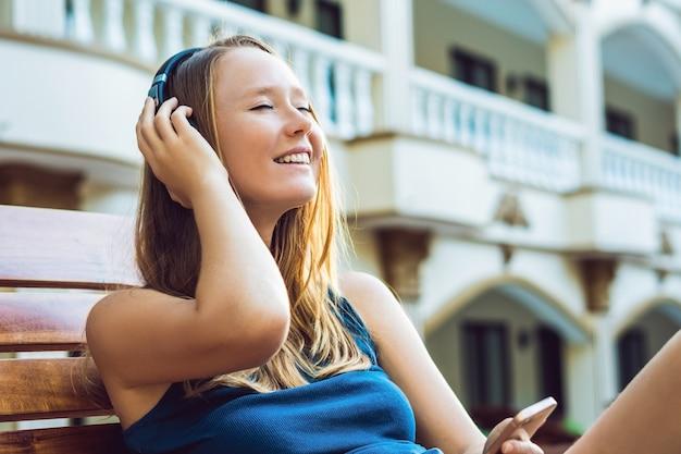 ストリーミング音楽をイヤフォンで聞いてプールの近くでリラックスした幸せなスマートフォンの女性。携帯電話アプリ4gデータを使用してリラックスしながら曲を再生する美しい少女