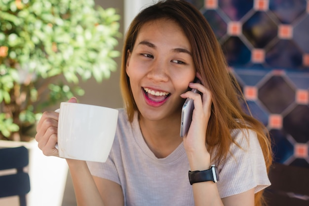Happy smile asian business women using talking cell phone sitting in cafe and holding a cup of coffe