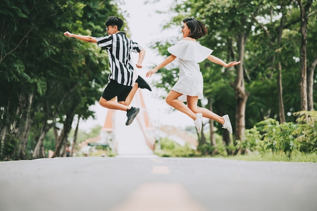 Happy smile asian lesbian couple jumping off the ground outdoor in the park.