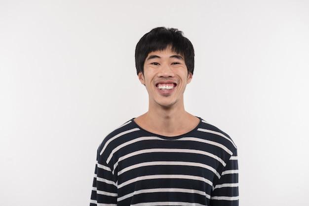 幸せな笑顔。白い背景に立っている間あなたを見ている陽気なアジア人