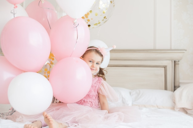 Happy smile child girl with bare heels holds bundles of balloons children birthday copy space mock