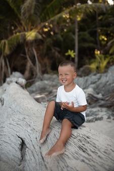 Счастливый улыбающийся европейский белокурый мальчик отдыхает и сидит на пляже с белым песком