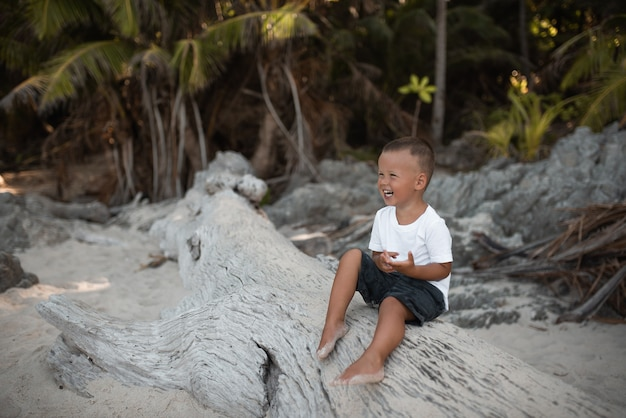 Happy smile european blond baby boy have rest and sit on white sand beach
