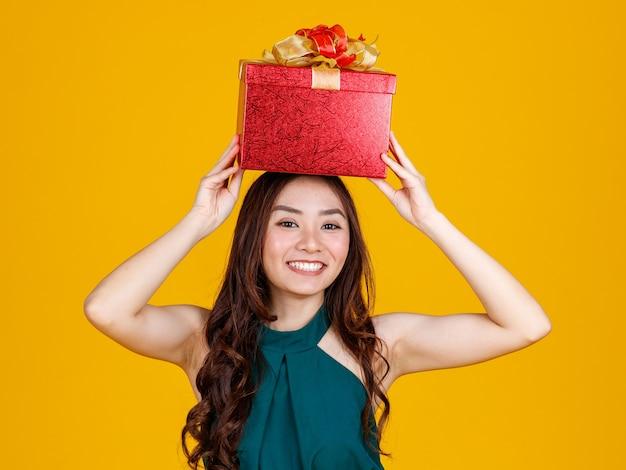 Счастливая улыбка сталкивается с милой азиатской девушкой с темными волосами, держащими подарочную коробку над головой с восхитительной и взволнованной съемкой студии на желтом фоне. отпразднуйте и концепцию фестиваля.