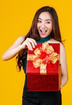 Счастливая улыбка сталкивается с симпатичной азиатской девушкой с темными волосами, держащей подарочную коробку с восхитительной и взволнованной студией на желтом фоне. отпразднуйте и концепцию фестиваля.