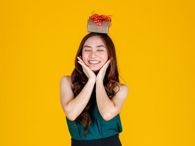 幸せな笑顔の顔黒髪のかわいいアジアの女の子は、黄色の背景で楽しくて興奮したスタジオショットで頭にギフトボックスを置きます。祝うとお祭りのコンセプト。