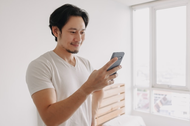 Happy and smile face of man using smartphone