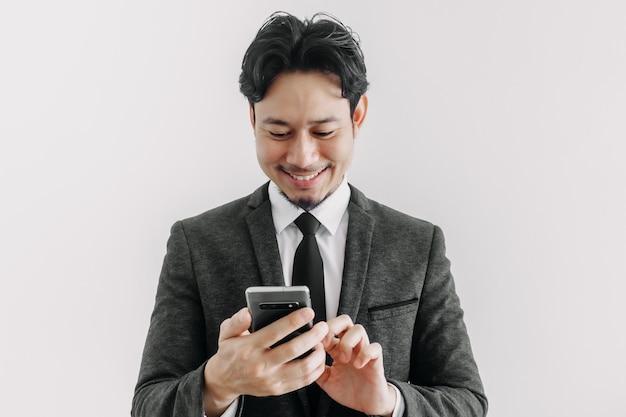 Счастливое улыбающееся лицо бизнесмена использует смартфон в концепции торгового приложения