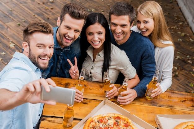 自撮りのための幸せな笑顔!屋外に立っている間、ビールとボトルを保持し、スマートフォンで自分撮りを作る若者のグループの上面図