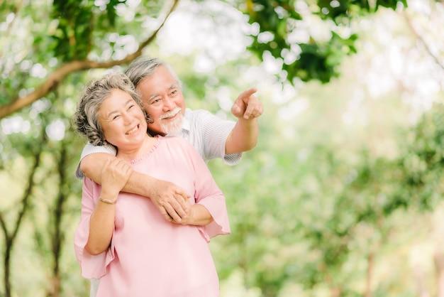 公園で一緒に楽しい時間を過ごして恋に幸せな笑顔のシニアアジアのカップル。女性を抱きしめる男
