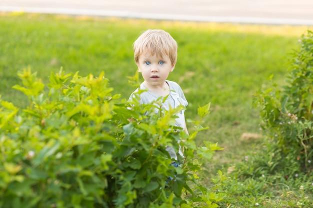Счастливая улыбка малыша мальчик гуляет в парке на открытом воздухе