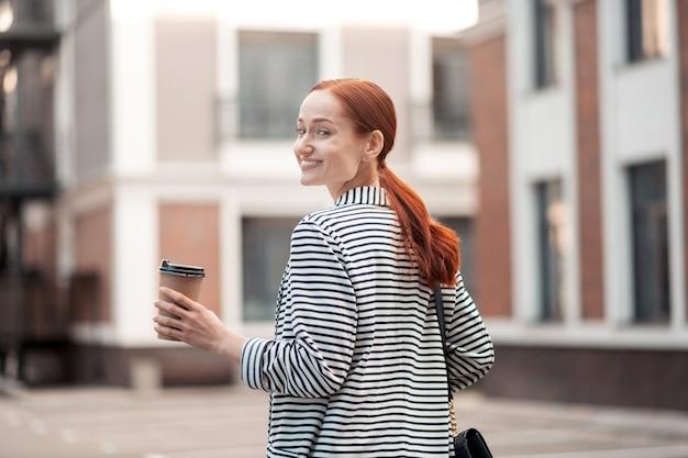 幸せな笑顔。屋外で彼女の肩越しに振り返りながらコーヒーの紙コップを保持している笑顔の若い女性のウエストアップ