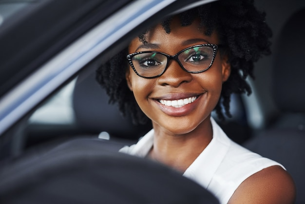 Happy smile. young african american woman sits inside of new modern car.