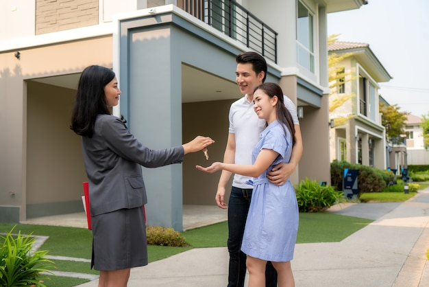 Happy smile young couple take keys new big house from real estate agent