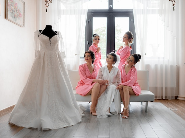 Счастливые улыбающиеся подружки невесты смотрят на свадебное платье в светлой комнате, подготовка к свадьбе