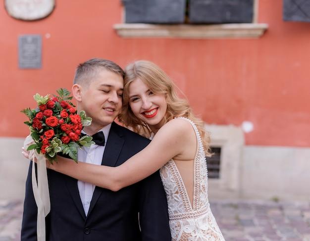 Счастливая улыбающаяся пара свадьбы обнимает перед красной стеной на открытом воздухе, день свадьбы, официальный брак