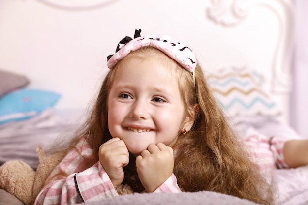 Happy smiles redhead girl child is lying on the bed sheets on the huge bed dressed in pink pajamas