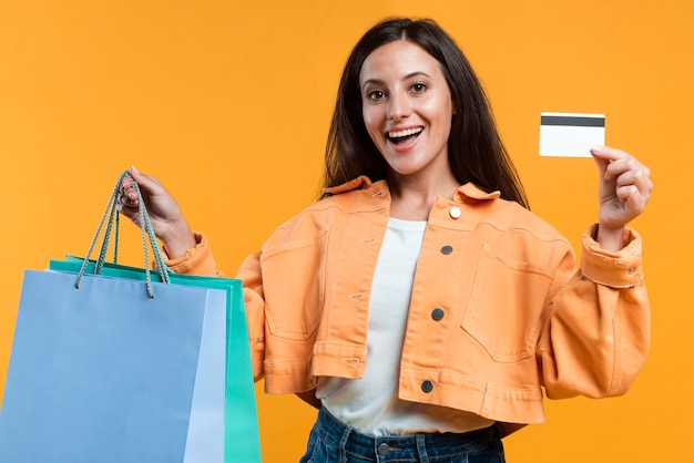 Happy smiley woman holding up credit card and shopping bags