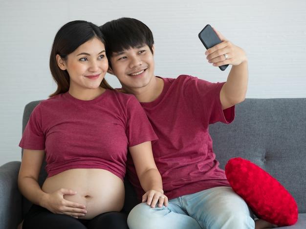幸せな笑顔の若いカップルは、ソファに座って一緒に笑顔でセルフィーをしているカジュアルな服を着ています。彼らは健康な赤ちゃんを期待しています。妊娠と家族の概念。