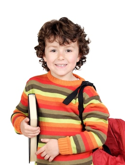 Happy smiling 8 year-old boy with backpack and a book ready to go to school isolated on white background with copy space