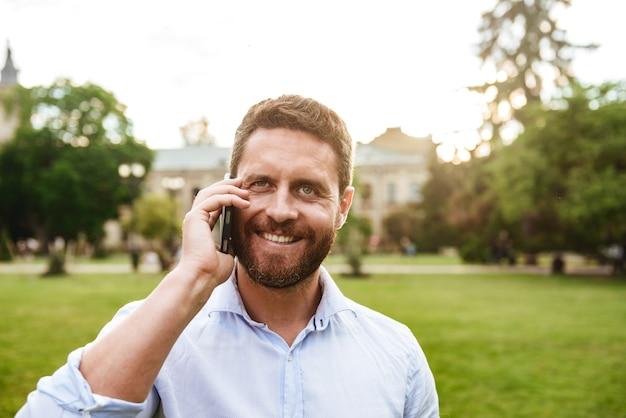 녹색 공원에서 산책하는 동안 검은 스마트 폰으로 이야기하는 동안 당신을 찾고 흰 셔츠에 행복 웃는 성인 남자