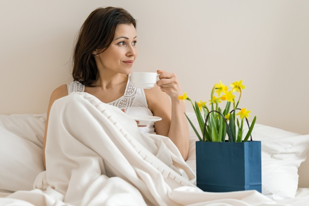 Happy smiling adult woman with bouquet of yellow flowers and cup of coffee sitting at home in bed.