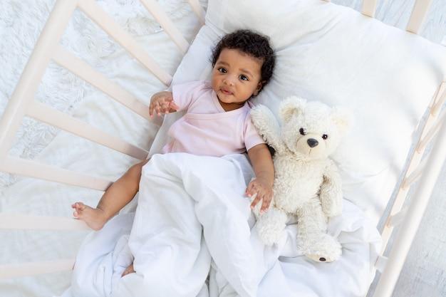 테디 베어와 함께 침대에서 행복 웃는 아프리카 계 미국인 아기가 잠에 빠지거나 침대에 간다