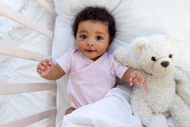 테디베어와 함께 침대에서 웃고 있는 행복한 아프리카계 미국인 아기가 잠들거나 잠자리에 든다