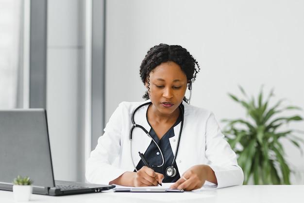 Счастливая улыбающаяся афро-американская женщина-врач или медсестра с гарнитурой и ноутбуком, имеющие конференц-связь или видеозвонок в больнице