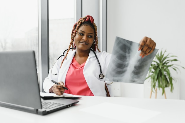 Счастливая улыбающаяся афро-американская женщина-врач или медсестра с гарнитурой и ноутбуком, имеющая конференц-связь или видеозвонок