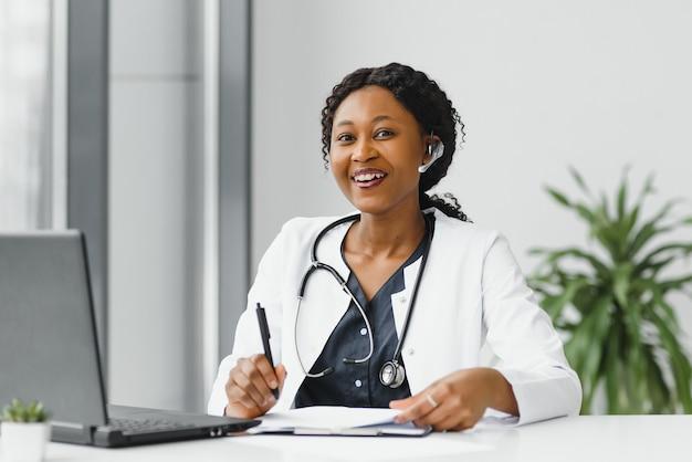 Счастливая улыбающаяся афро-американская женщина-врач или медсестра с гарнитурой и ноутбуком, имеющая конференц-связь или видеозвонок Premium Фотографии