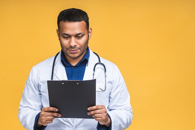 Happy smiling african american indian black doctor man writing recipe on clipboard, isolated over yellow background.