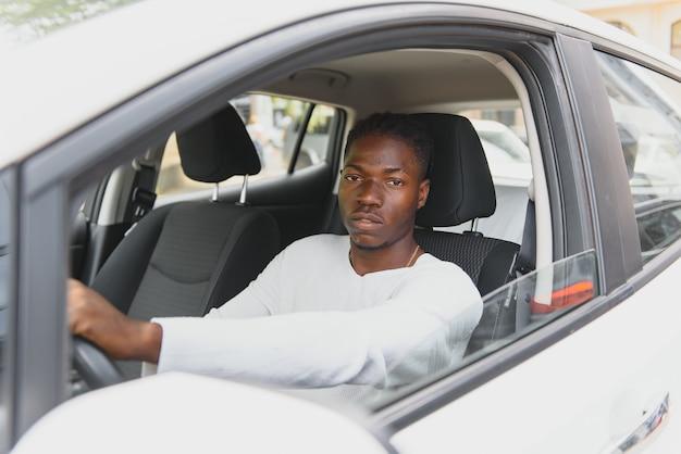 Счастливый улыбающийся афро-американский водитель-мужчина, сидящий за рулевым колесом автономного современного электрического автомобиля. счастливый парень держит телефон и улыбается в камеру в современном электромобиле