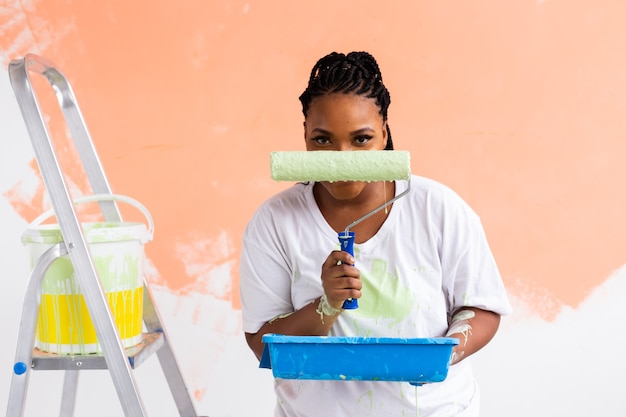 Happy smiling african american woman painting interior wall of new house. redecoration, renovation